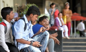 A pedestrian accesses the internet on his mobile phone in Bangalore