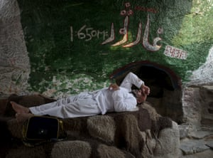 A pilgrim rests in front of the Thawr cave in the mountain.