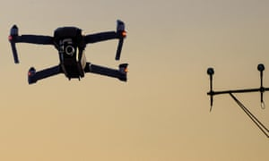 Unmanned drone flying near runway at airport in between approaching runway lighting at sunset.<br>RWXB3K Unmanned drone flying near runway at airport in between approaching runway lighting at sunset.