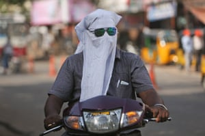 A man rides through the streets of Hyderabad with a cloth over his face to protect him from the heat