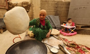 A Syrian refugee who fled her home in Raqqa cooks bread outside her tent during a sandstorm on Tuesday in a refugee camp in Bar Elias, Lebanon.