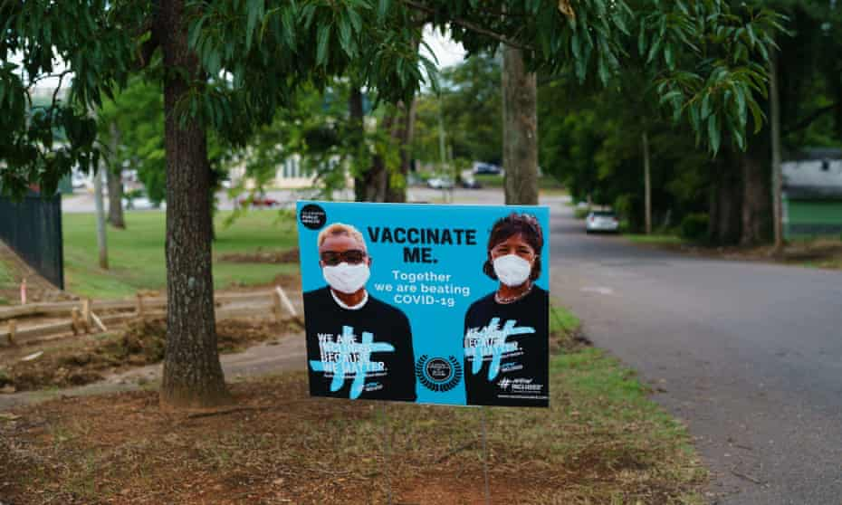 A sign encouraging Covid-19 vaccination is seen outside a park on in Birmingham, Alabama.