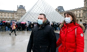 Tourists wearing protective masks walk past the Louvre museum in Paris, which remained closed on Monday after staff exercised their 'right to withdraw' their labour after concerns about the number of tourists, reportedly from Asia, entering wearing masks