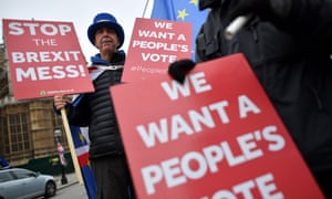 """Anti-Brexit demonstrators hold placards calling for a """"People's Vote"""" outside the Houses of Parliament."""