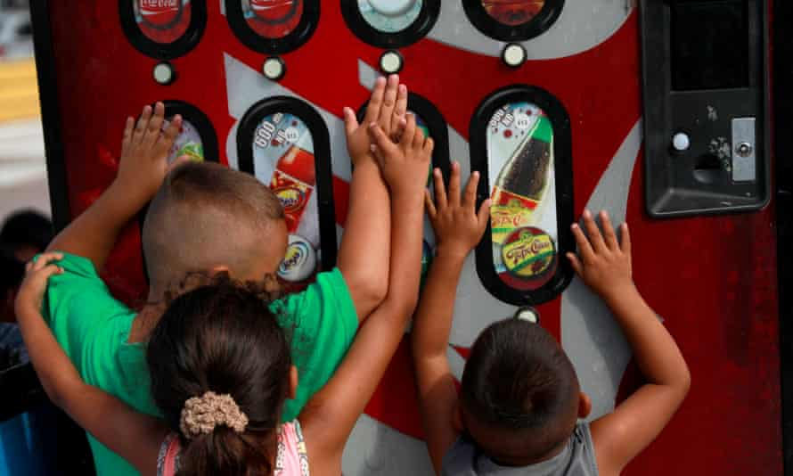 children play with a soda dispenser in mexico