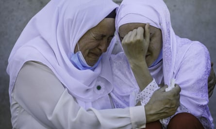 A daughter of a victim of Srebrenica genocide is hugged by her mother