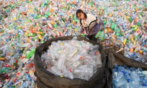 A woman sorts through bottles at a recycling centre in Beijing.