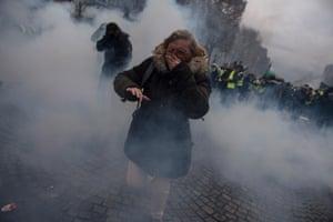 A woman flees through a cloud of tear gas.