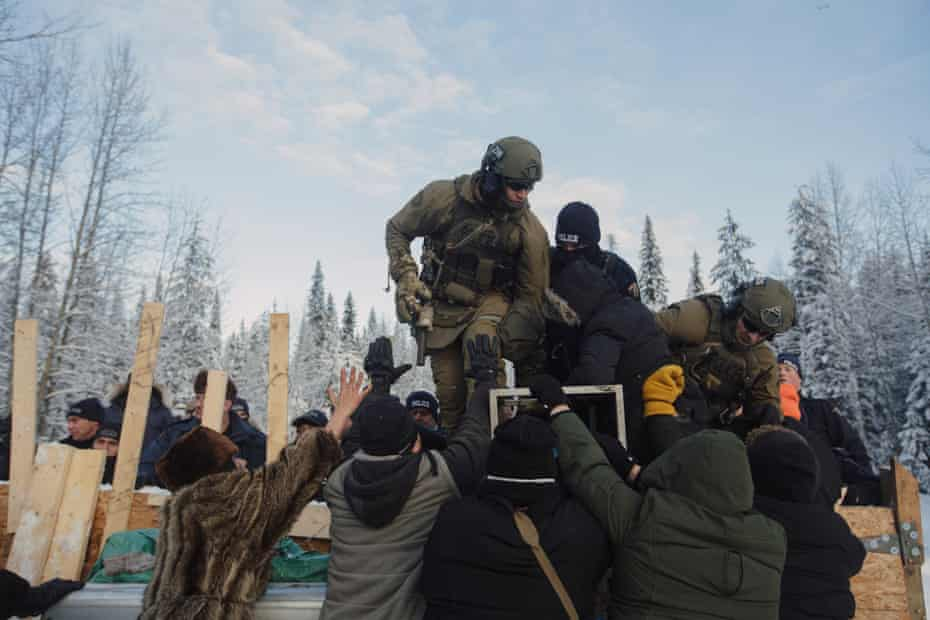 Police climb over a barricade to enforce the injunction filed by Coastal Gaslink Pipeline at the Gidimt'en checkpoint near Houston, British Columbia on Monday, January 7, 2019. The pipeline company were given a permit but the Office of the Wet'suwet'en, who have jurisdiction over the territory in question, have never given consent. Fourteen people were arrested. Amber Bracken for The New York Times
