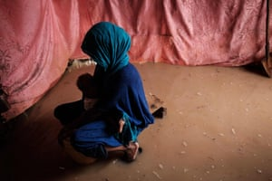 A woman holds her baby in a flooded shelter at the Dadaab refugee complex, north-eastern Kenya