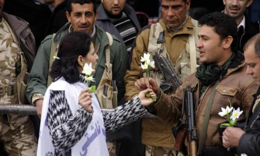 A woman hands flowers to soldiers in Sulaymaniyah in the Kurdish region of Iraq during a demonstration