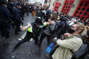 Police officers attempt to control the crowd.