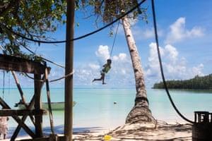 Boy swings on a tree in Tuvalu