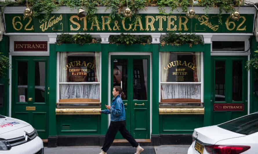 A woman walks past a temporarily closed pub in London