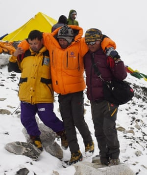 Rescuers assist an injured at Everest base camp.
