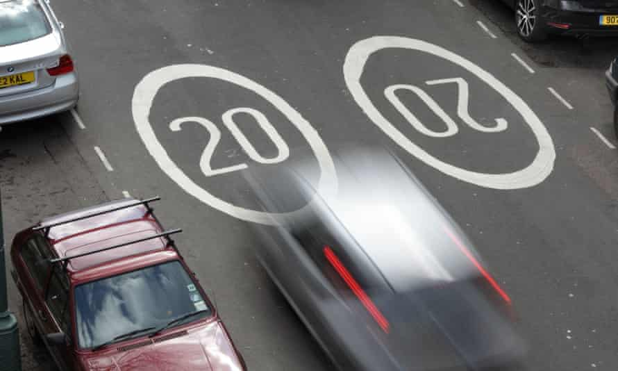 20 mph speed limit markings on a road with speeding cars.