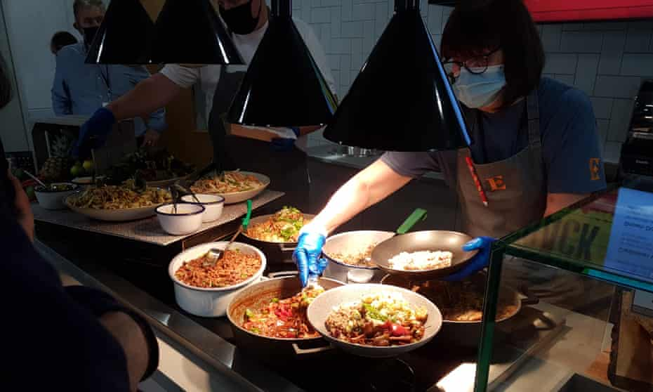 People helping themselves to food in a cafeteria.