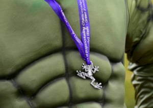 A man dressed as the Hulk proudly displays his medal