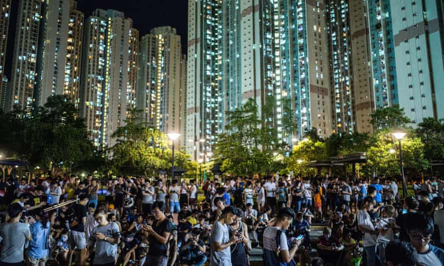 Pokémon Go players gather under night lights against a backdrop of skyscrapers at the game's Hong Kong launch in 2016.