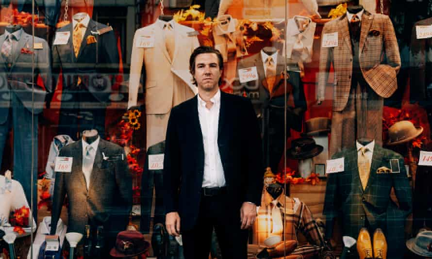 Hamilton Leithauser in a suit outside a shopfront selling suits