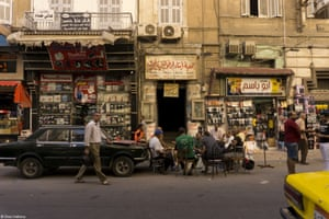 Men gather on the side of a street in old Alexandria to share the gossip with a cup of black sweet tea and snacks. This is a common sight in Egypt where their national drink, tea, is enjoyed throughout the day