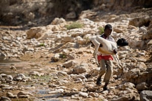 Eid, a young boy, carries one of his sheep down to a river to drink near Hargeisa, capital of Somaliland