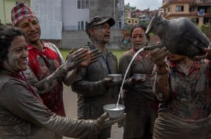 Farmers pour traditional drink in a paddy field on National Paddy Day in Tokha village, on the outskirt of capital Kathmandu, Nepal