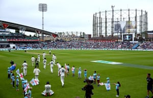 The Australian players and England's batsmen Rory Burns and Joe Denly of England take to the field.