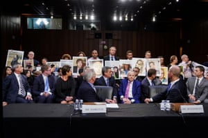 John Hamilton, vice president and chief engineer of Boeing, and chief executive Dennis Muilenburg look back at family members holding photographs of Boeing 737 crash victims as they testify before a Senate commerce, science and transportation committee hearing.
