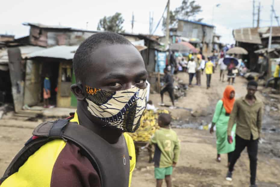 A boda-boda, or motorcycle taxi, driver wears a makeshift mask made from a local fabric known as Kitenge as he looks for customers in the Kibera neighbourhood of Nairobi
