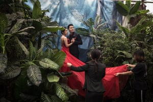 Assistants hold a bride's red dress as she poses together with her groom