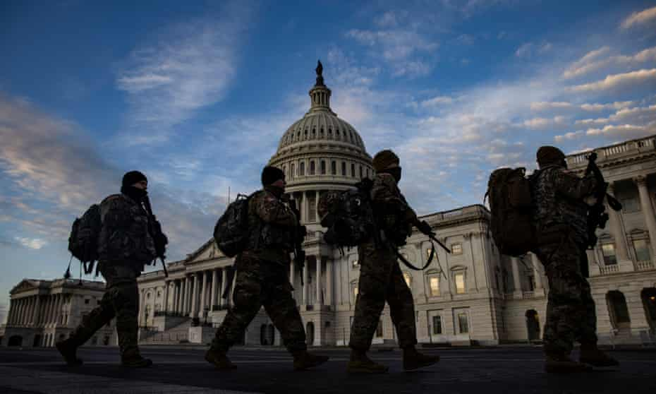 National Guard troops march past the US Capitol building as day breaks in Washington, DC, on 14 January.