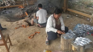 Xieng Pheang, 48, and his wife Toiy Pheang, 43, make utensils at their home in Ban Napia.