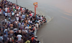 Residents watch the flood peak at the flooded river bank of Longwangmiao water area where the Yangtze River and Hanjiang River converge, on July 28, 2010 in Wuhan of Hubei Province, central China.