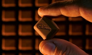 Square of Cadbury chocolate held between finger and thumb, more chocolate in background.