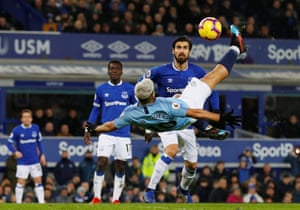 Manchester City's Sergio Aguero shoots at goal with a overhead kick as Everton's Andre Gomes looks on.