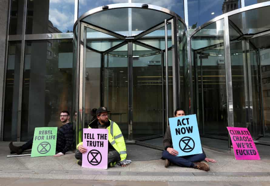 Protesters glue their hands to the ground outside the London Stock Exchange