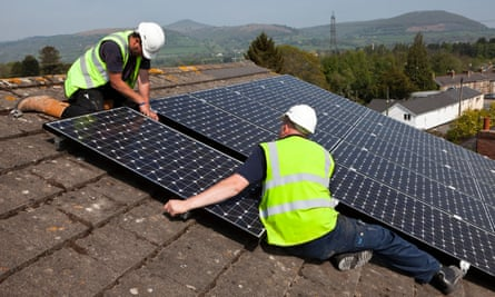 Workers install solar panels on a roof in Wales