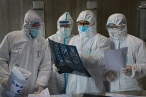 Xiaogan, ChinaMedical workers in protective suits inspect a CT scan image at a hospital in Yunmeng county in Hubei, the province hit hardest by the novel coronavirus outbreak
