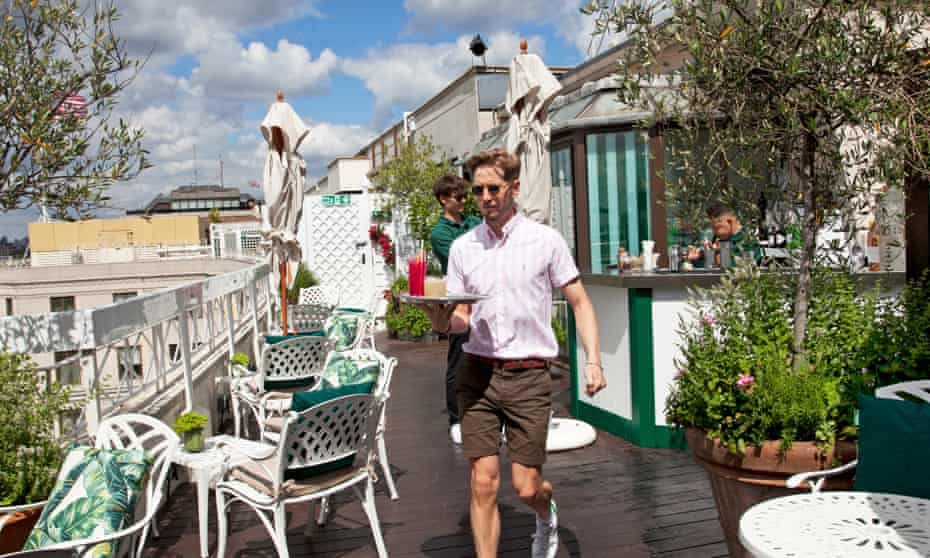 A waiter carrying a tray on the rooftop restaurant