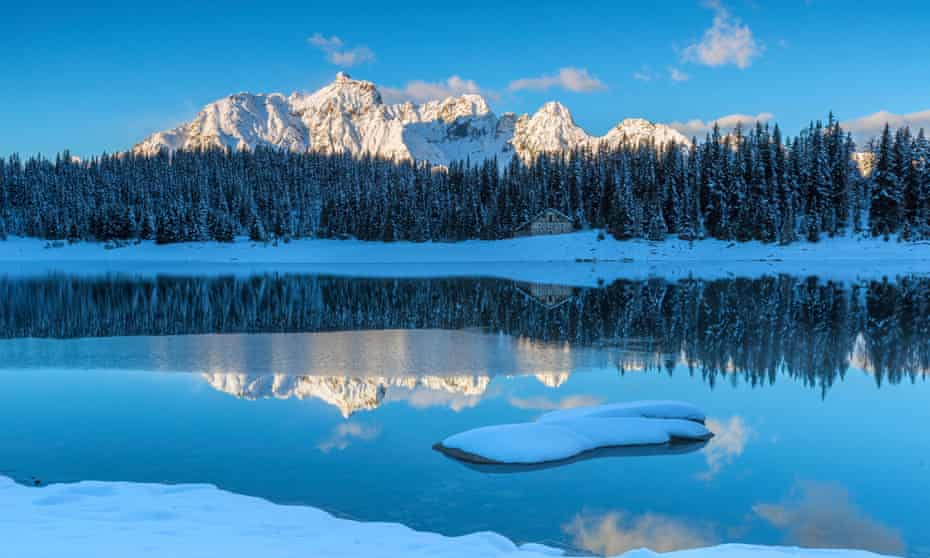 Wooden cabin surrounded by snowy peaks and woods reflected in Lake Palu at dawn, Malenco Valley Valtellina, Lombardy, Italy Europe.