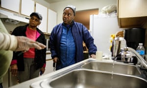 A handyman explains the new water filter to Mary Stewart and Terrence Tyler at their residence in Flint, Michigan.