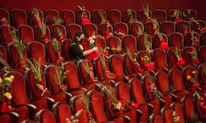 An opera employee wearing a protective face mask arranges flowers on the audience seats prior to the opera La Traviata by Italian composer Giuseppe Verdi, at the Sofia Opera, in Sofia, on 18 February 2021.