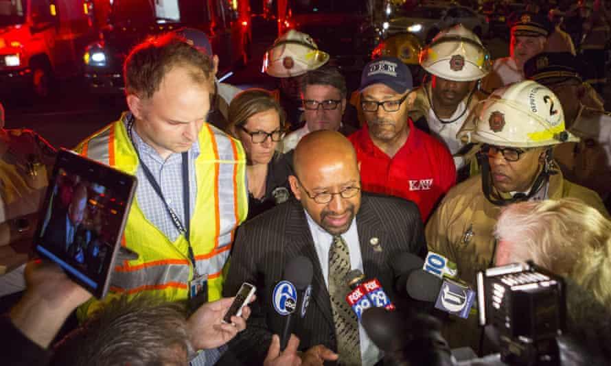 Michael Nutter, centre, mayor of Philadelphia speaks to reporters at the scene of the train crash.