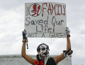 """Fonz Tobin, 25, from Albuquerque, N.M., holds up a sign in front of the Lincoln Memorial in Washington, as he joins other supporters of the rap group Insane Clown Posse, during a rally Saturday, Sept. 16, 2017, to protest and demand that the FBI rescind its classification of the juggalos as """"loosely organized hybrid gang.""""(AP Photo/Pablo Martinez Monsivais)"""