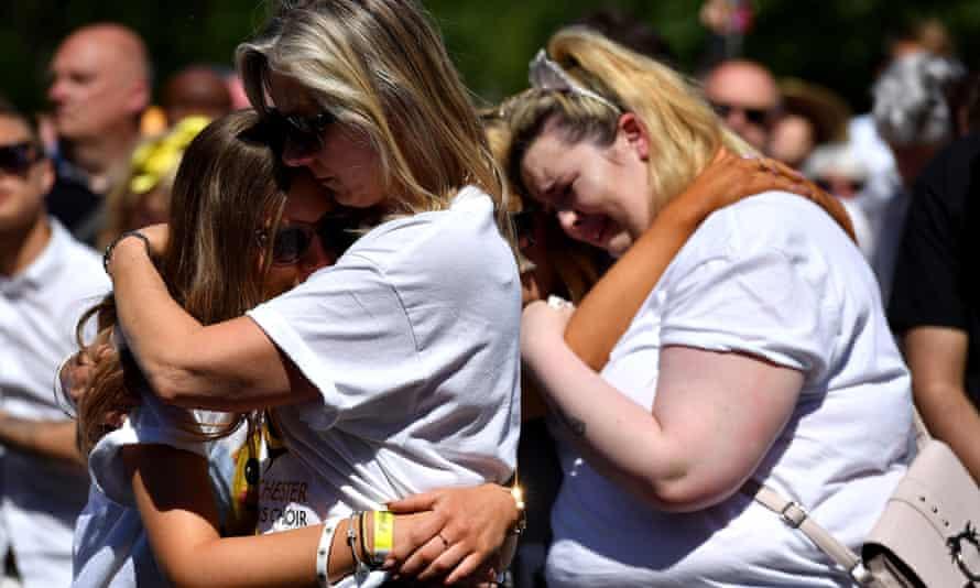 Two tearful blonde women hug children in bright sunshine