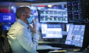 A trader in shirtsleeves and a face mask sits at a desk with several display screens in front of him