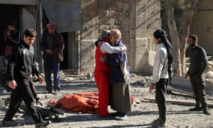 Syrians comfort each other on 19 November, following a reported air strike on Aleppo's rebel-held neighbourhood of Bab al-Nayrab.
