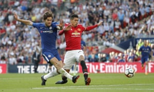Marcos Alonso shoots under pressure from Chris Smalling.