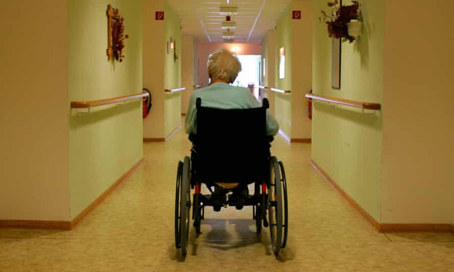 Old man in a wheelchair in the corridor of a retirement home, facing away from the camera